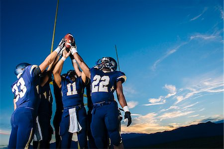 football team - Teenage and young male american football team celebrating and holding up ball Stock Photo - Premium Royalty-Free, Code: 614-08030968