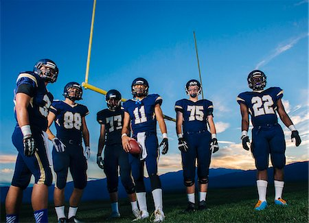 football team - Portrait of teenage and young male american football team on pitch Stock Photo - Premium Royalty-Free, Code: 614-08030970