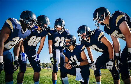 football team - Teenage and young male American football team gathering and planning at practice Stock Photo - Premium Royalty-Free, Code: 614-08031092