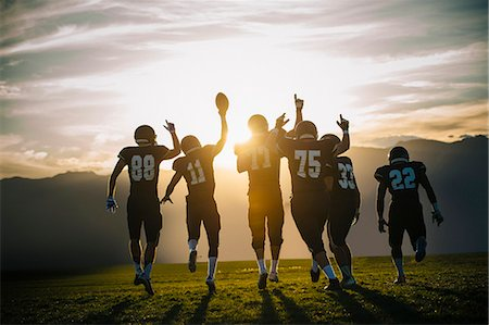Rear view of teenage and young male american football team celebrating at sunset Stock Photo - Premium Royalty-Free, Code: 614-08031108