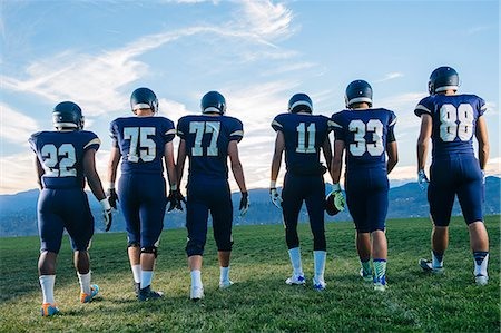 football team - Rear view of teenage and young adult american football team in a row Stock Photo - Premium Royalty-Free, Code: 614-08031101