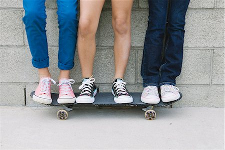 Three girls standing on skateboard, low section Stock Photo - Premium Royalty-Free, Code: 614-08031142