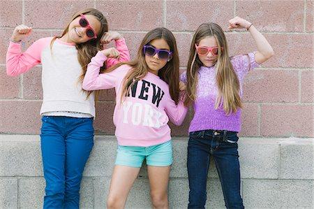 Three girls flexing muscles Stock Photo - Premium Royalty-Free, Code: 614-08031143
