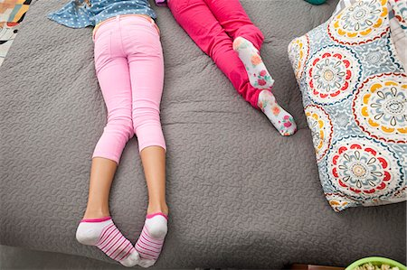 Two girls lying on bed, low section Stock Photo - Premium Royalty-Free, Code: 614-08031175