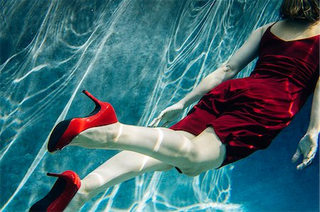 refraction - Mature woman wearing red dress and high heels, swimming, underwater view Stock Photo - Premium Royalty-Free, Code: 614-08065884