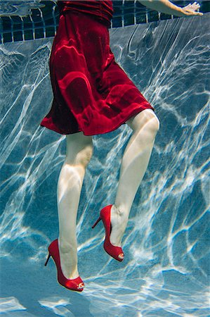refraction - Mature woman wearing red dress and high heels, underwater view, low section Stock Photo - Premium Royalty-Free, Code: 614-08065885
