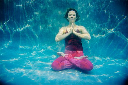 refraction - Mature woman wearing red yoga pants and vest, in yoga position, underwater view Stock Photo - Premium Royalty-Free, Code: 614-08065886