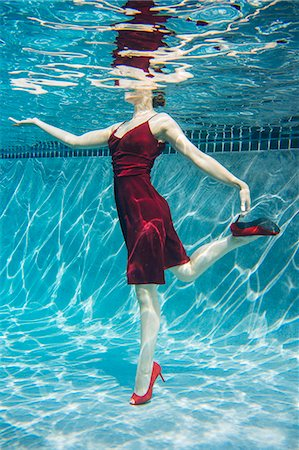 Mature woman wearing red dress and high heels, standing on one leg, underwater view Stock Photo - Premium Royalty-Free, Code: 614-08065888