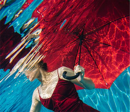 refraction - Mature woman wearing red dress, holding red umbrella, underwater view, mid section Stock Photo - Premium Royalty-Free, Code: 614-08065889