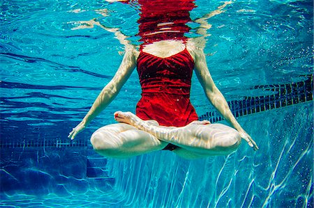 refraction - Mature woman wearing red dress, legs crossed, underwater view, low section Stock Photo - Premium Royalty-Free, Code: 614-08065883