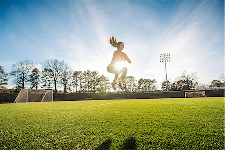Young female athlete doing jump training on sports field Stock Photo - Premium Royalty-Free, Code: 614-08065916