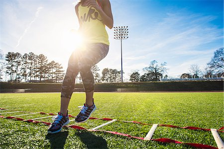Neck down view of female athlete training with agility ladder on sports field Stock Photo - Premium Royalty-Free, Code: 614-08065926