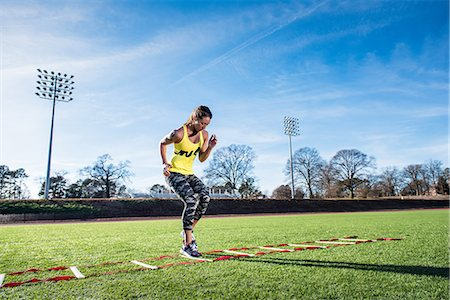 Young female athlete training with agility ladder on sports field Stock Photo - Premium Royalty-Free, Code: 614-08065928