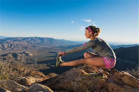stretch - Rear view of young female trail runner crouching and touching toes,Pacific Crest Trail, Pine Valley, California, USA Stock Photo - Premium Royalty-Free, Code: 614-08066012