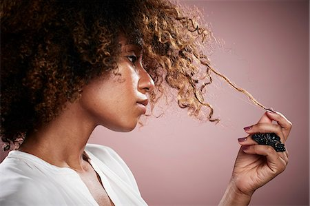 pulling - Portrait of young woman pulling on strand of curly hair Stock Photo - Premium Royalty-Free, Code: 614-08066080