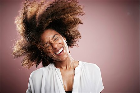 Portrait of young woman flicking hair, smiling Stock Photo - Premium Royalty-Free, Code: 614-08066081