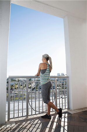 fitness   mature woman - Mature woman in sports clothing looking out from city balcony Stock Photo - Premium Royalty-Free, Code: 614-08066137
