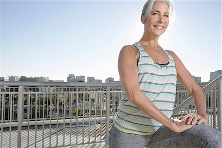 fitness   mature woman - Portrait of mature woman doing warm up exercises on city balcony Stock Photo - Premium Royalty-Free, Code: 614-08066138