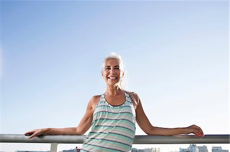 Portrait of mature woman in sports clothing leaning against city balcony Stock Photo - Premium Royalty-Free, Code: 614-08066139
