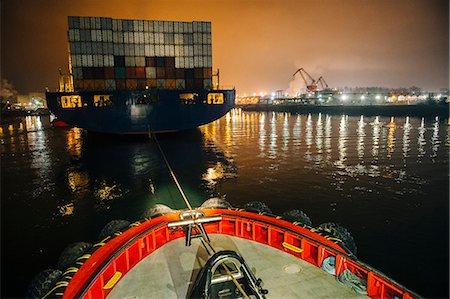 pulling - Tugboat manoeuvring cargo ship in harbor at night, Tacoma, Washington, USA Stock Photo - Premium Royalty-Free, Code: 614-08066155