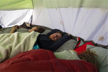 Three young adult friends asleep in tent Stock Photo - Premium Royalty-Free, Code: 614-08081219
