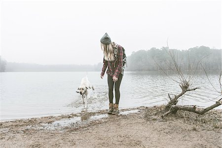 Young woman playing with her dog on misty lakeside Stock Photo - Premium Royalty-Free, Code: 614-08081225