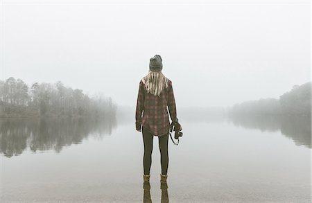 Young woman with camera standing in misty lake Stock Photo - Premium Royalty-Free, Code: 614-08081228
