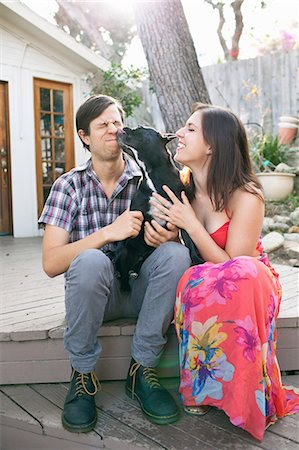 Young couple sitting on patio with dog licking face Stock Photo - Premium Royalty-Free, Code: 614-08081243