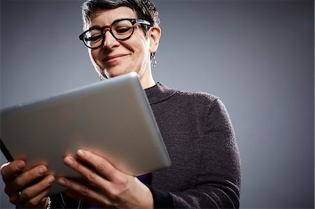 Studio portrait of mature businesswoman reading digital tablet Stock Photo - Premium Royalty-Free, Code: 614-08081363