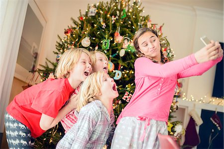 Teenage girl and brothers taking smartphone selfie at christmas Stock Photo - Premium Royalty-Free, Code: 614-08081392