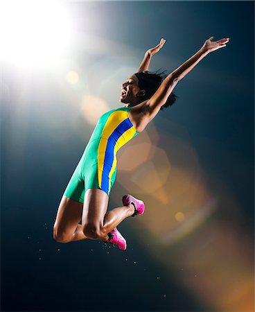 Young female athlete jumping mid air in celebration in stadium Stock Photo - Premium Royalty-Free, Code: 614-08081435