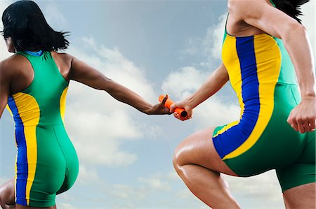 Two female relay athletes exchanging baton whilst running Stock Photo - Premium Royalty-Free, Code: 614-08081439