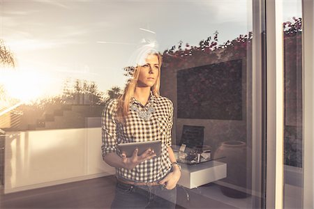 Portrait of young woman with digital tablet gazing from suburban window Stock Photo - Premium Royalty-Free, Code: 614-08081432