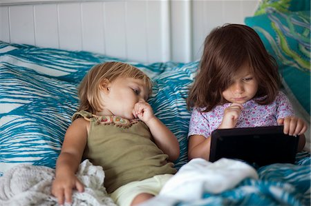elementary age - Girl and toddler sister reclining in bed using digital tablet Stock Photo - Premium Royalty-Free, Code: 614-08081440