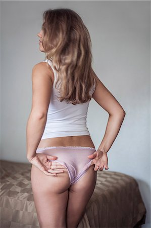 Backview of woman adjusting knickers Stock Photo - Premium Royalty-Free, Code: 614-08119514