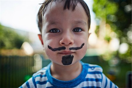 Close up portrait of boy looking at camera wearing beard and moustache face paint costume Stock Photo - Premium Royalty-Free, Code: 614-08119549