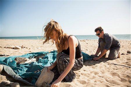 Couple setting up tent on beach, Malibu, California, USA Stock Photo - Premium Royalty-Free, Code: 614-08119556
