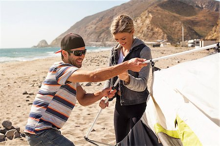 Couple setting up tent on beach, Malibu, California, USA Stock Photo - Premium Royalty-Free, Code: 614-08119552