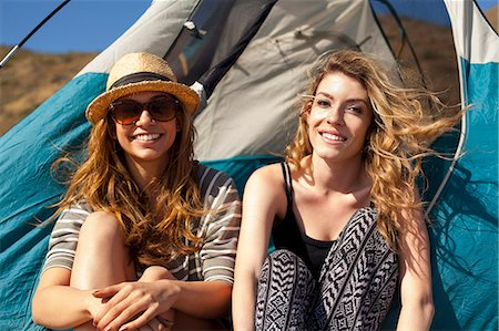 Girlfriends relaxing beside tent Stock Photo - Premium Royalty-Free, Code: 614-08119561