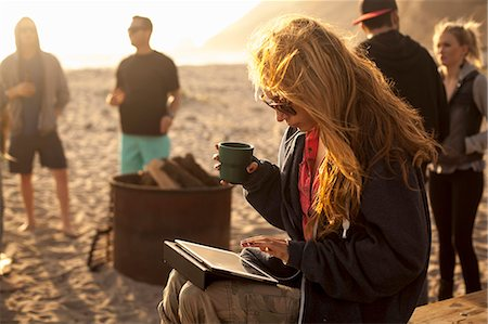 Woman using digital tablet on beach, friends in background Stock Photo - Premium Royalty-Free, Code: 614-08119592