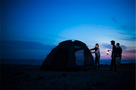 Group of friends setting up tent on beach at sunset Stock Photo - Premium Royalty-Free, Code: 614-08119616