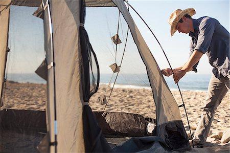 Man setting up tent on beach, Malibu, California, USA Stock Photo - Premium Royalty-Free, Code: 614-08119619