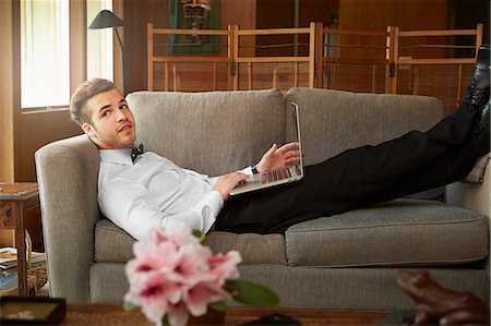 Portrait of man wearing smart clothes laying on sofa using laptop Stock Photo - Premium Royalty-Free, Code: 614-08119696