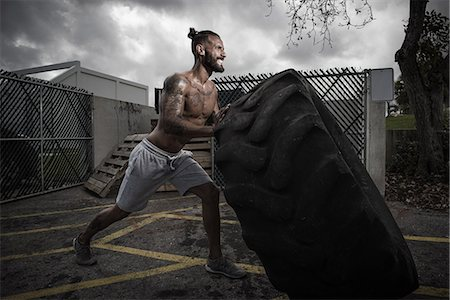 physical fitness - Male boxer with gritted teeth pushing truck tyre in yard Stock Photo - Premium Royalty-Free, Code: 614-08119886