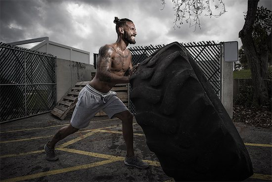Male boxer with gritted teeth pushing truck tyre in yard Stock Photo - Premium Royalty-Free, Image code: 614-08119886
