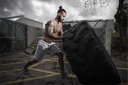 Male boxer training with truck tyre in yard Stock Photo - Premium Royalty-Free, Code: 614-08119887