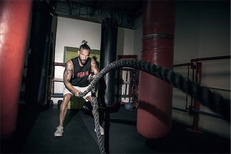 Male boxer doing battle rope training in gym Stock Photo - Premium Royalty-Free, Code: 614-08119900