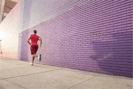 Rear view of male runner running along sidewalk Stock Photo - Premium Royalty-Free, Code: 614-08126725