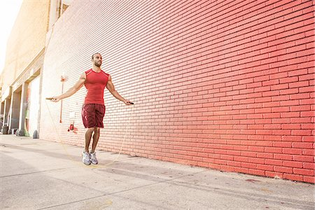 sports - Male runner skipping on sidewalk Stock Photo - Premium Royalty-Free, Code: 614-08126727