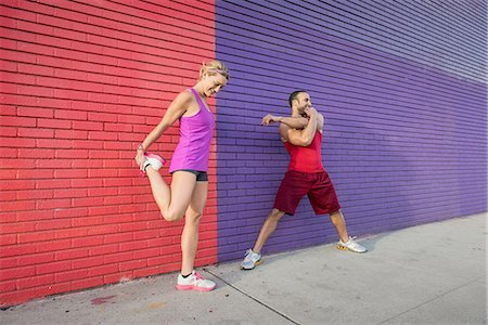 Male and female runners warming up on sidewalk Stock Photo - Premium Royalty-Free, Code: 614-08126729